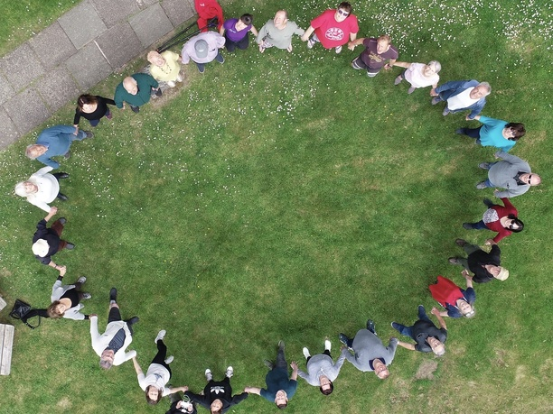 An ariel picture from a drone of adults in a circle joining hands and looking up