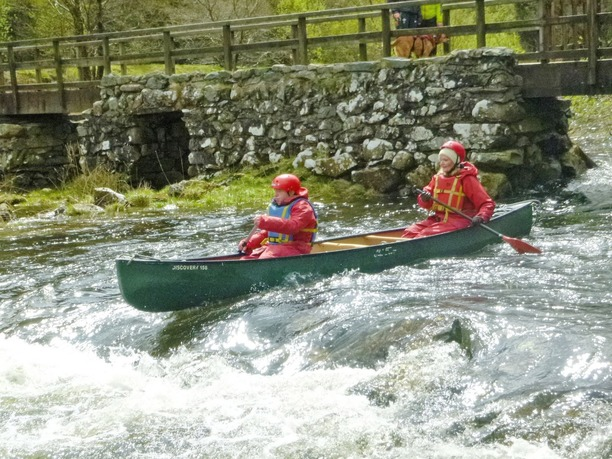 2 adults in a canoe on white water